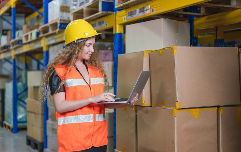 Female worker wear safety vest and yellow helmet with  laptop checking goods stock in warehouse factory