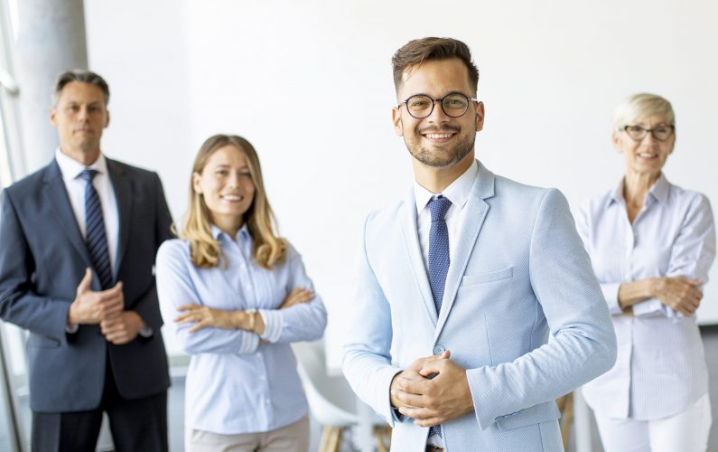 Group of a businesspeople standing together in the office with their young bussines leader