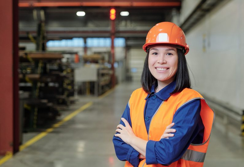 Portrait of smiling confident young Asian factory engineer in orange hardhat and vest standing in workshop
