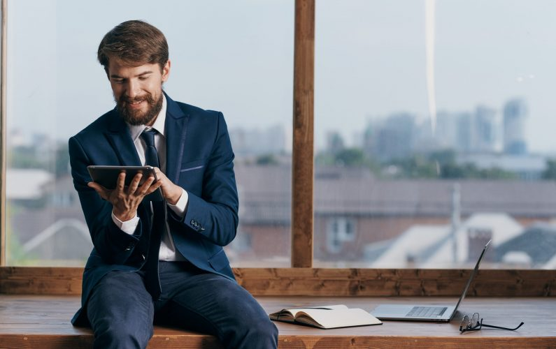A man in a suit with a tablet in the hands of an office official, a professional businessmen. High quality photo