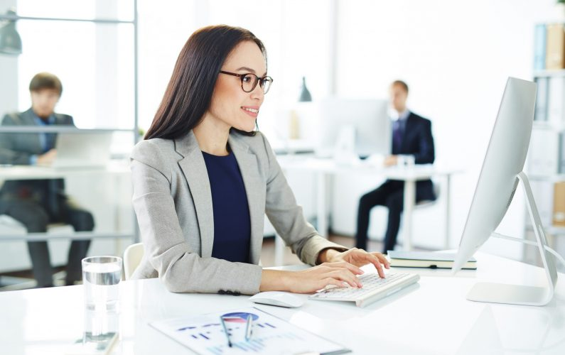 Smiling accountant entering data in office