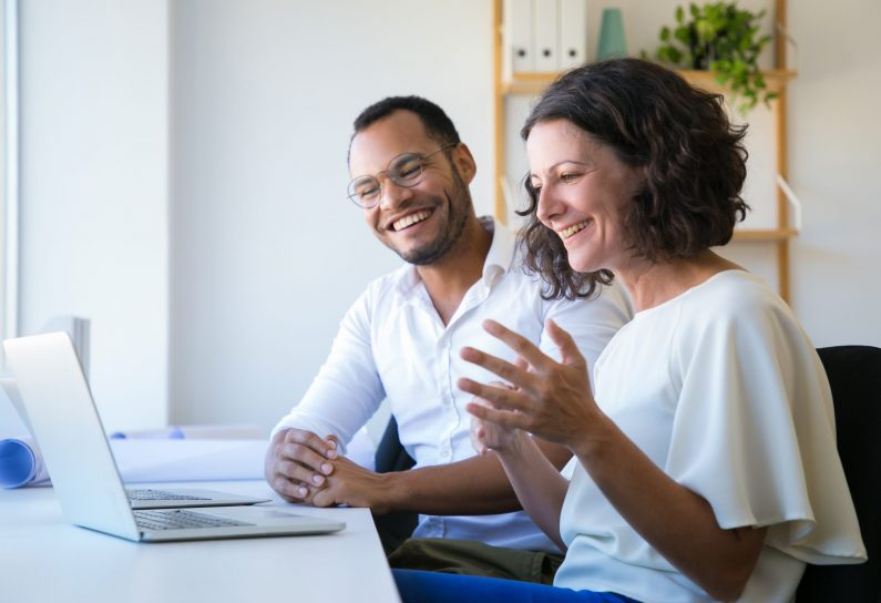 Cheerful colleagues using laptop for video call. Man and woman sitting at workplace together, looking at monitor and laughing. Communication concept