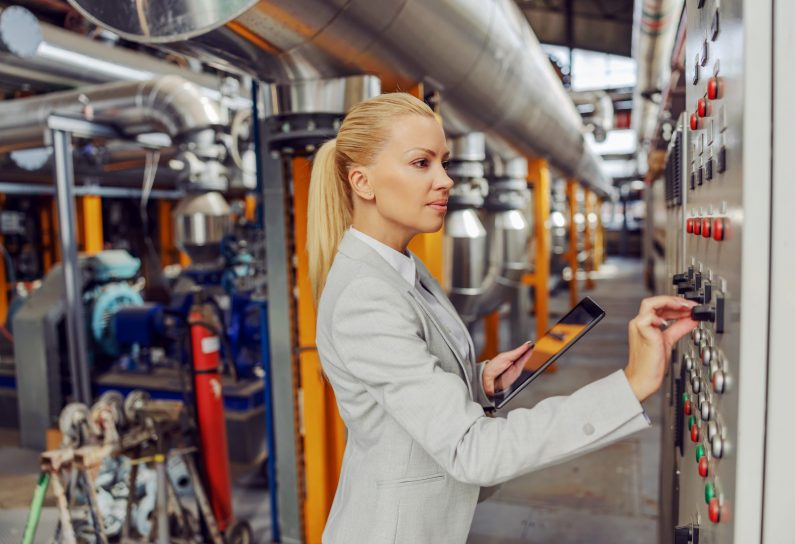 Female blond supervisor standing in heating plant next to dashboard, adjusting settings and holding tablet.