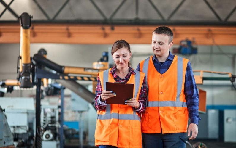 Male and Female Industrial worker use tablet and Walking Through Heavy Industry Manufacturing Factory. They Wear Hard Hats and Safety Jacket