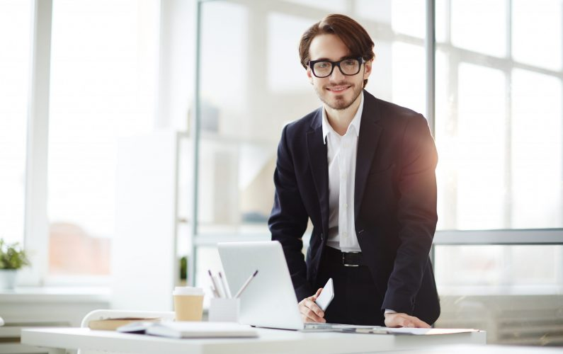 Young manager in formalwear leaning over workplace while standing up or sitting down