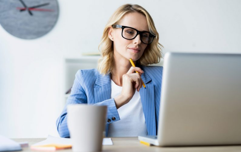 Portrait of a serious businesswoman using laptop in bright modern office