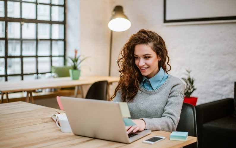Successful young woman in modern office working on laptop.